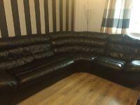 Corner black leather sofa and single armchair