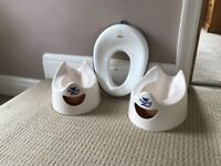 Two pourty potties and a toilet training seat