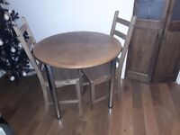Round solid wood table with metal legs plus 3 wooden chairs .