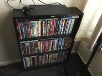 Small black bookcase with over 100 DVDs plus a player to play them on.