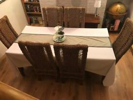 Solid wooden table and 6 wicker chairs. Dining table and chairs