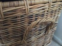 Wicker basket with handles and leather straps.