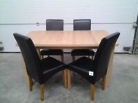 New Extendable dining table and 4 chairs (black faux). Boxed Can deliver.