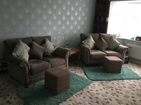 Two 2 seater sofas in light brown colour with 2 foot stools and cushions
