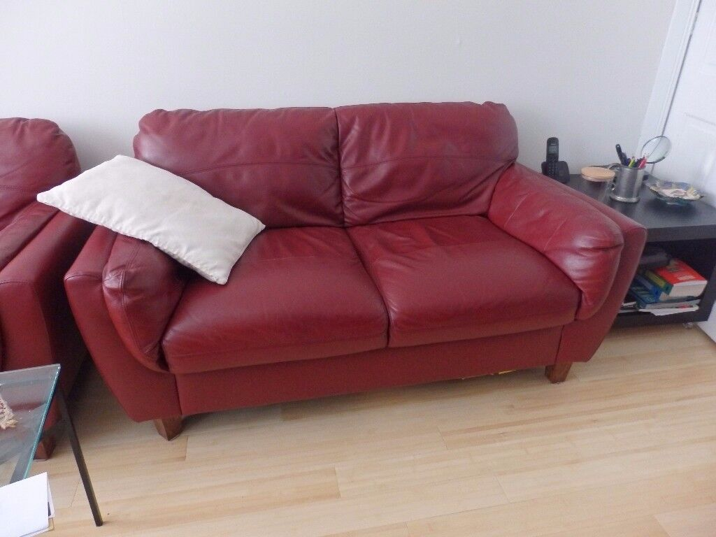 Two identical burgundy leather sofas