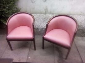 Two curved chairs with light pink leather