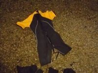 child's wetsuit and 2 pairs of shoes