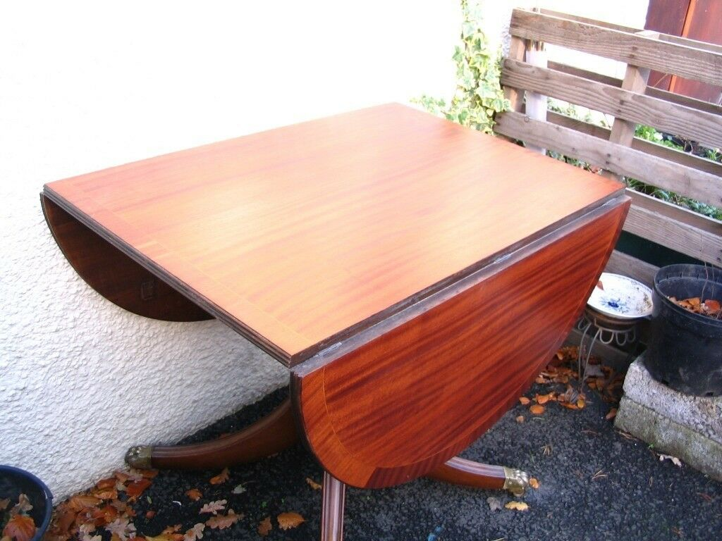 antique table, single pedestal base drop leaf side oval top, solid mahogany, brass castors, 6 seater