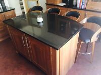 A dress/display cabinet, black granite work top island with integrated fridge and freezer.