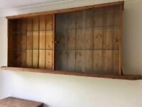 Pine wall mounted display cabinet with glass sliding doors.