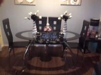 Black and silver glass dining table with 4 black leather chairs