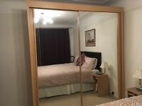 Double wardrobe with sliding mirror doors