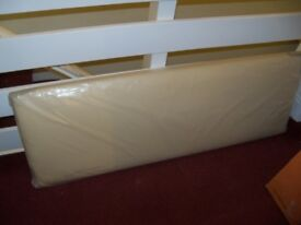 DOUBLE HEADBOARD. NEVER USED. STILL WRAPPED. FAUX/LEATHER? CREAM COLOUR. £22 ONO. NEED SPACE