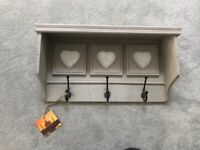 Distressed finish taupe wooden shelf with coat hooks