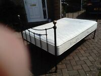 Black metal framed double bed stead frame with wooden slats and thick mattress