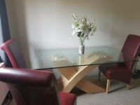 Large glass dining table with wooden curved base