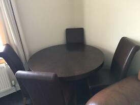 Brown, circular wooden dining table & 4 brown leather chairs