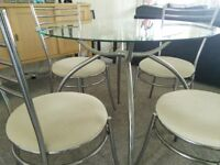 Glass n chrome dining table and 4 cream upholstered chairs, 900mm diameter, good condition.