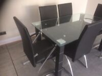 Stylish glass dining table including 6 black faux leather chairs
