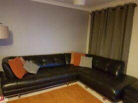 large black leathet corner sofa, atmchair and storage footstool