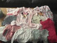 Selection of baby girl tops, dresses and onesies.