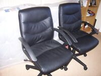 Two black office desk chairs on wheels.