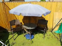Garden or bistro table with chairs and parasol.