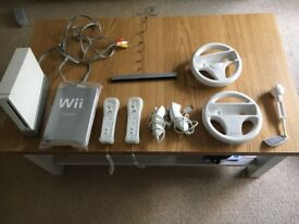 Wii Console, complete with 2 controllers, 2 steering wheels, 2 nun chucks & 12 x games,