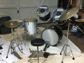 Drum set including bass drum with 2 tom toms attached. 5 drums + 4 symbols and seat.