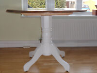 A circular pine table on a detachable white painted plinth