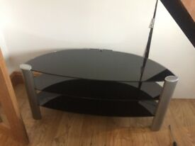 Black glass tv stand with silver coloured legs good condition