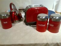 all red funky toaster and whistle kettle(non-electric) and tea coffee and sugar tins