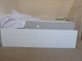 super king bed base with four large draws and pocket spring mattress with white sitting sheets.