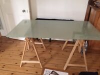 Glass top trestle table in good condition