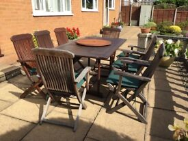 Large Outdoor table with 8 folding chairs, green seat pads, market umbrella and Lazy Susan.