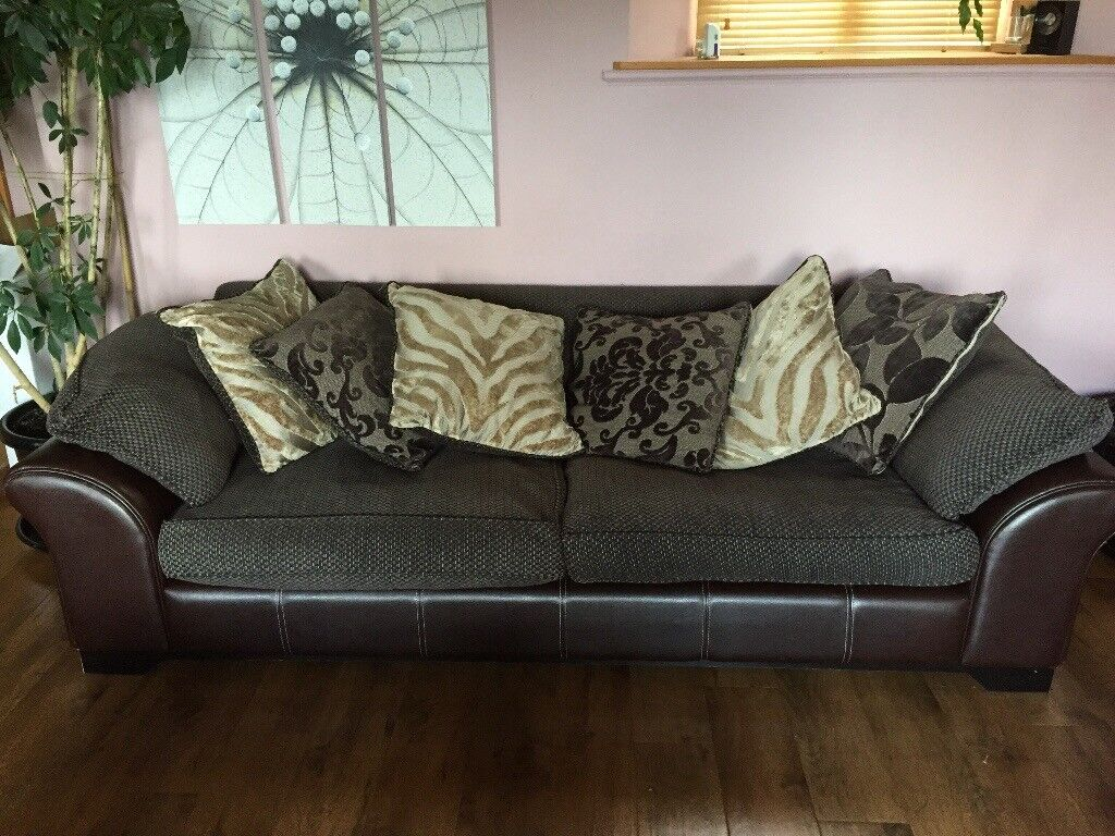 Four seater sofa. Slightly worn on the arms. Six or more feather cushions.