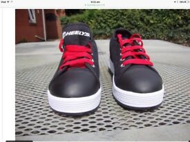 Heeleys black and red shoes with 2 wheels in size 3.