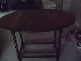 Small oval dark wood table. Drop leaf. Good condition.