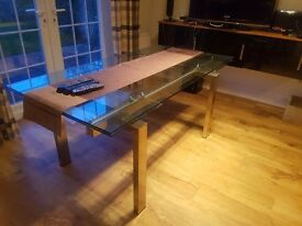 Glass table with extendable ends. Will sit 6 and 8 comfortably when fully extended.