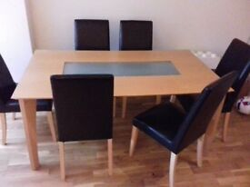 Light wood table with frosted glass insert, with 6 faux leather black chairs.