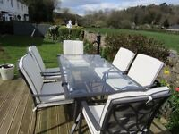 Garden table and six armchairs with cream cushion backs and seats