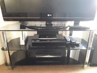 A black glass TV stand with chrome legs.