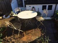 Metal garden table and three folding decorative chairs.