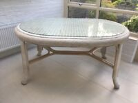 White dining table with separate plate glass top in ivory coloured rattan finish