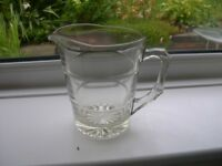 A heavy duty one litre capacity clear glass jug.