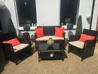 Black rattan garden furniture with cream cushions