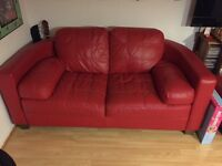 Red leather curved sofas with footstool