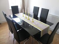 Black glass dining table with six faux leather and metal chairs