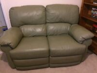 Green two piece, faux leather, reclining, sofa and arm chair set.