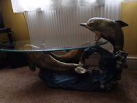 glass top coffee table with dolphin for sale